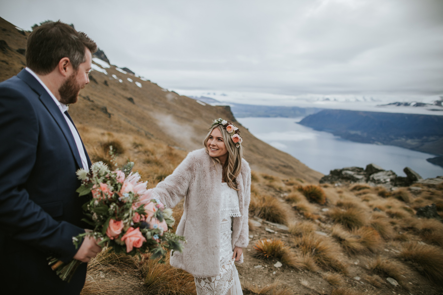 Mikaela and Tom walk together on Cecil Peak on their Queenstown wedding day. The mountains behind them are covered in cloud, but you can see the blue lake below them. With photography by Alpine Image Company