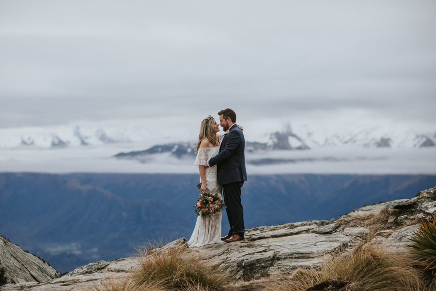 Mikaela and Tom stand on Cecil Peak on their wedding day. With photography by Alpine Image Company