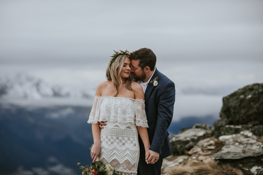 A bride and groom share a quiet moment on their Cecil Peak wedding. They fill the frame, but the mountains stand beautifully behind them. With photography by Alpine Image Company