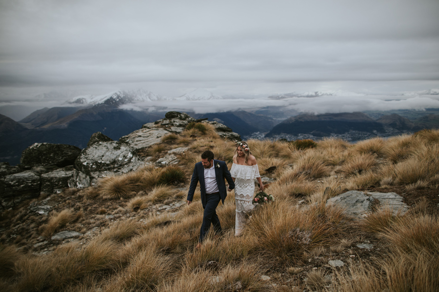 A bride and groom walk over tussock on Cecil Peak, on their wedding day. The sky is cloudy but you can see the beautiful Queenstown mountains behind them. With photography by Alpine Image Company