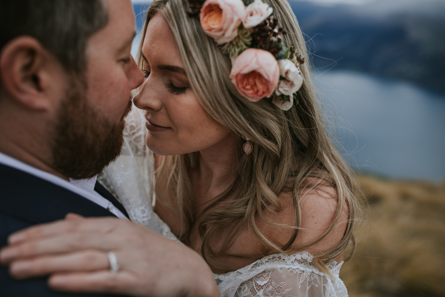 A gorgeous bride and groom relax together on their Cecil Peak elopement. The bride is wearing a stunning flower crown, and her fiance kisses her on the nose. With photography by Alpine Image Company