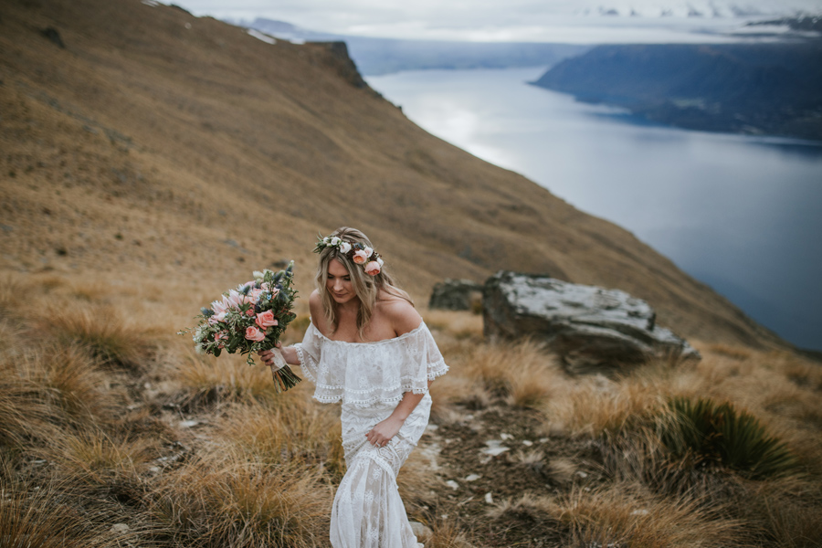 The gorgeous Mikaela walks along Cecil Peak on her wedding day. The lake in the background looks calm, and the mountains are covered in high cloud. With photography by Alpine Image Company