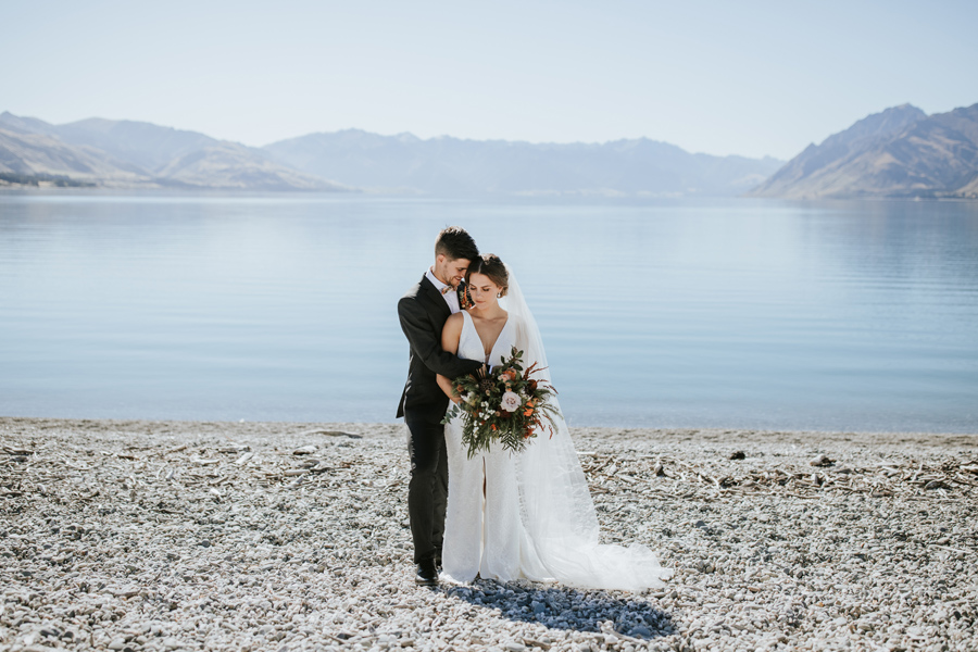 A bride and groom stand a hug infront of the beauitful, glacial blue Lake Hawea. The sun is shining and the mountains stand impressively in the background.With photography by Alpine Image Company