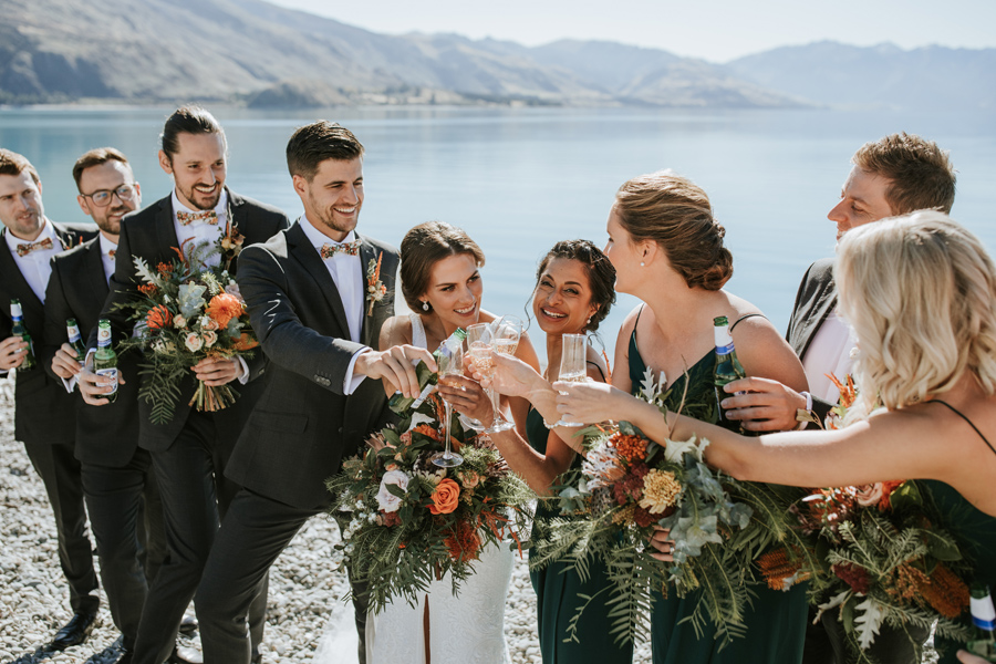 A bridal party toast the happy couple! The group stand in front of the glacial blue waters of Lake Hawea. There are mountains in the distance. With photography by Alpine Image Company