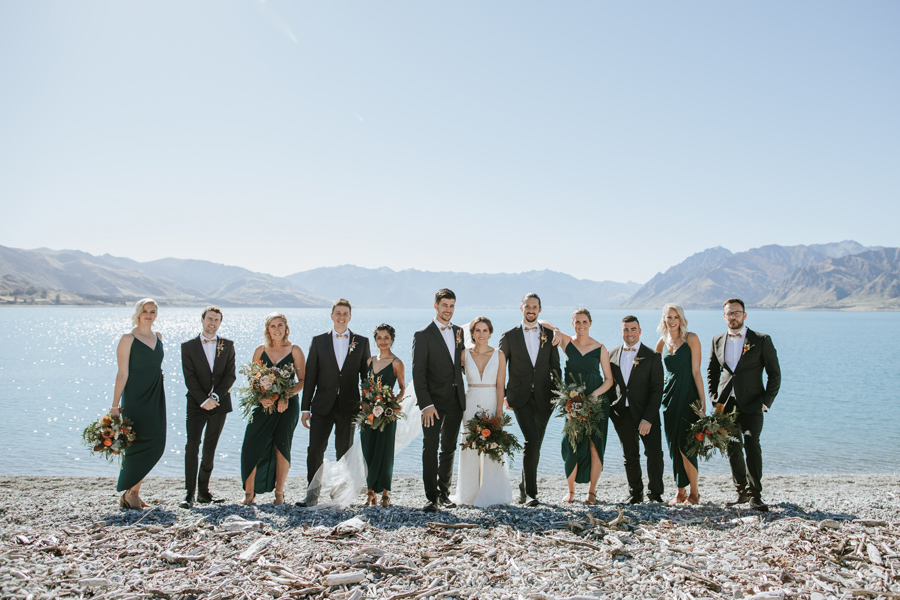 A bridal party smile for the camera on a beauitful blue sky wedding day. They stand infront of the pure blue glacial waters of Lake Hawea. With photography by Alpine Image Company