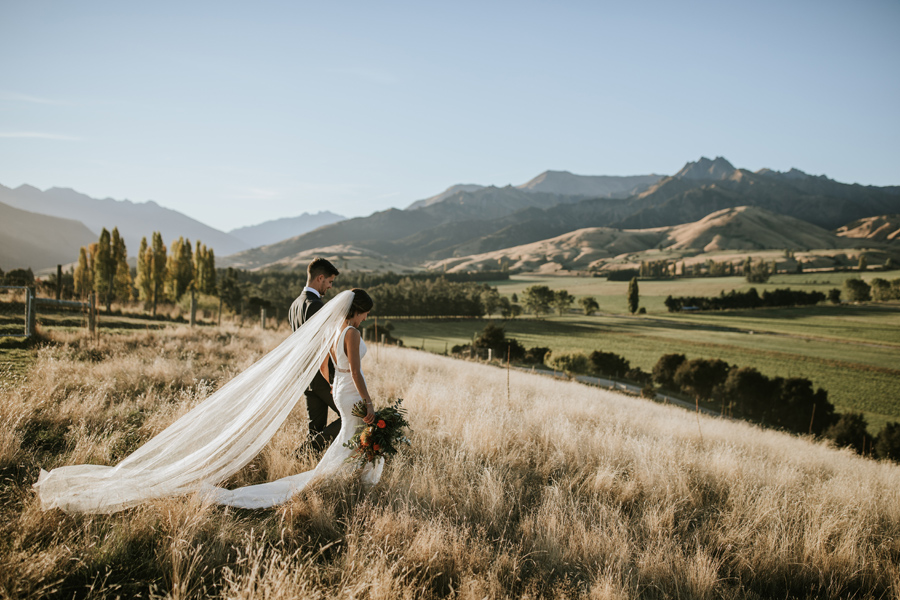 A bride and groom walk through golden fields. There are mountains behind them and the sky is blue. The brides veil flows out behind her. With photography by Alpine Image Company