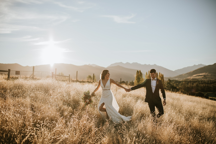 A bride leads her groom through a golden field at sunset. There are mountains behind, and they laugh with each other. With photography by Alpine Image Company