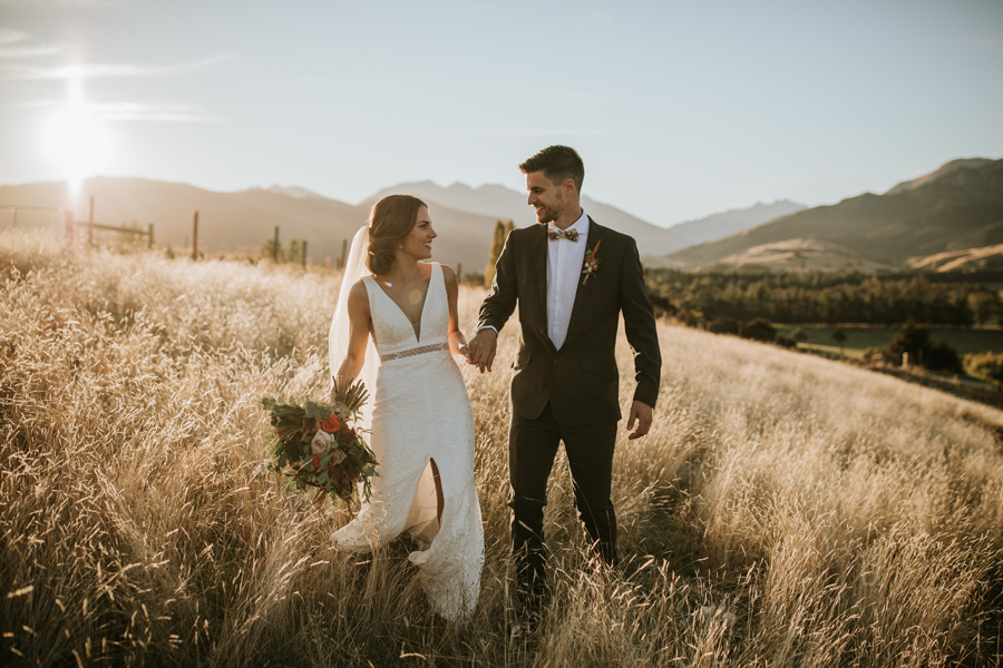 A bride and groom hold hands and smile at each other in a golden field on their Wanaka Wedding day. With photography by Alpine Image Company