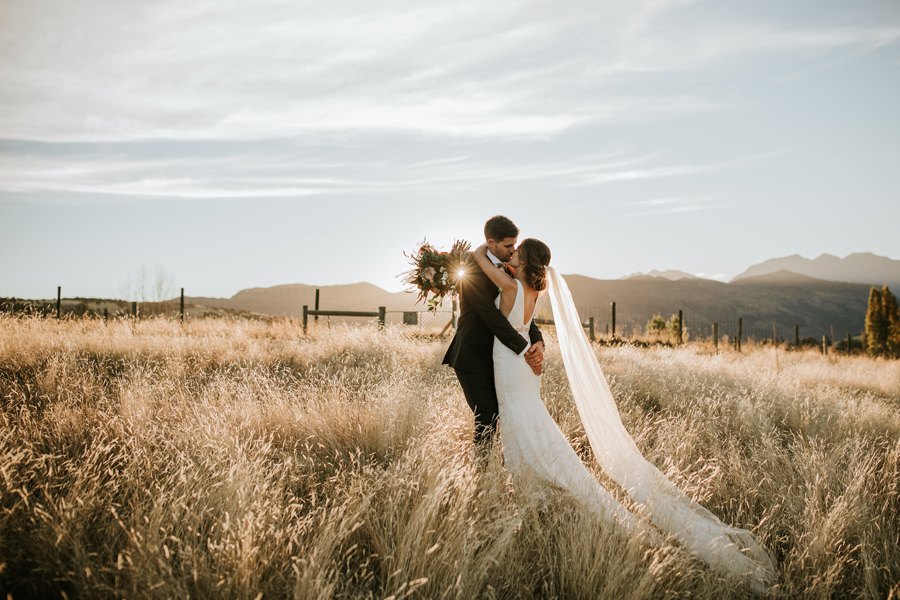A bride and groom embrace on their wedding day. They stand in a golden field as the sun sets behind them. With photography by Alpine Image Company