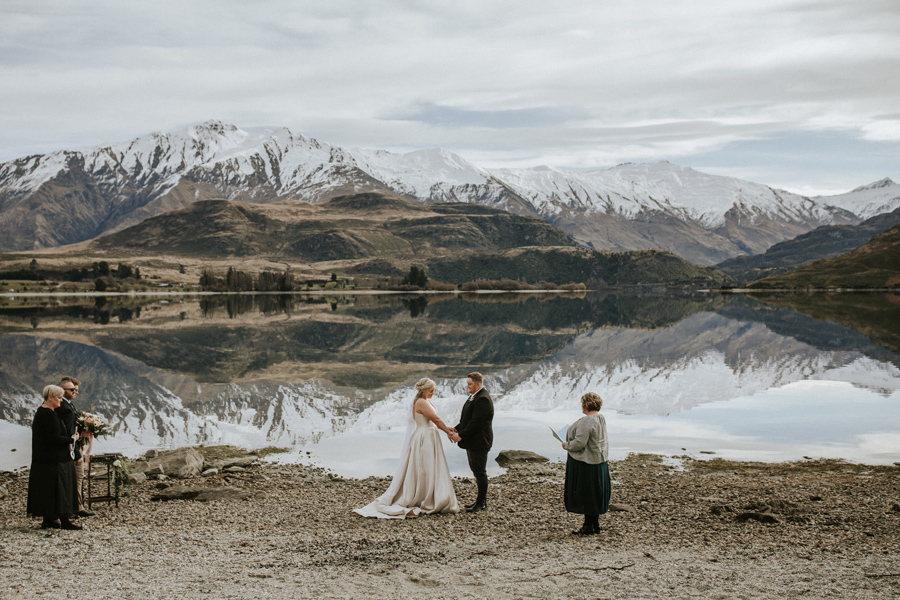This photo shows a wedding ceremony taking place in front of a beautiful lake. It is a calm day, and the lake is glassy. The snow capped mountains are reflected in the lake below, and it looks like a mirror.