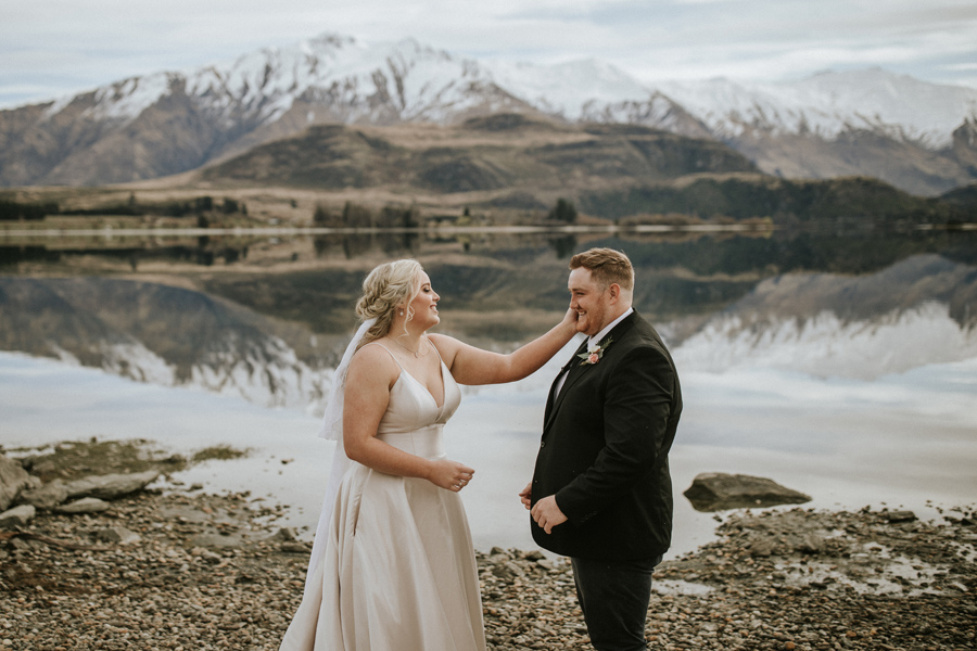 A bride wipes a tear from her grooms eye as they say their vows to each other on their wedding day. The stand in front of Lake Wanaka, with snow capped mountains in the background. With photography by Alpine Image Company