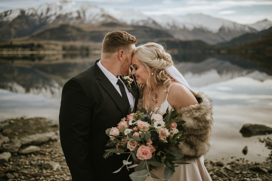 A couple share an intimate moment after saying 'i do' to one another. They are standing infront of Lake Wanaka on a beautifully calm day. The lake looks like a mirror, and the snow capped mountains are reflected in it. With photography by Alpine Image Company