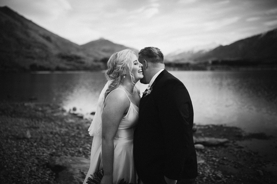 A couple laugh together on their wedding day by Lake Wanaka. This black and white image captures the authentic emotion and feeling of this moment. With photography by Alpine Image Company