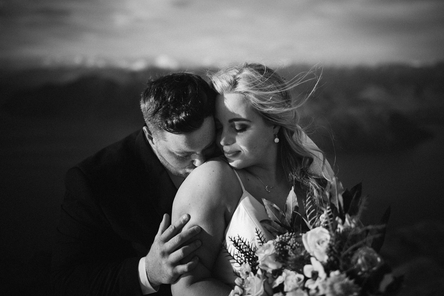 A couple share a windy embrace on top of a mountain, on their elopement wedding. With photography by Alpine Image Company