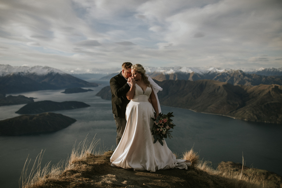 A couple stand on what looks like the top of the world, on their wedding day. The bride kisses the grooms hand, and the mountains and lake in the background look perfectly snowcapped and spectacular. With photography by Alpine Image Company