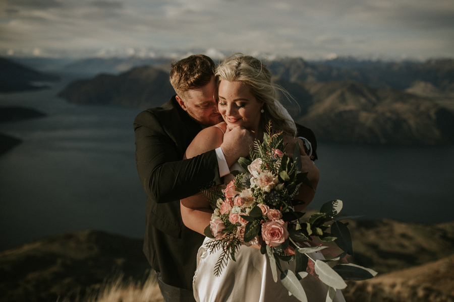 A groom brings his bride close for a kiss on their Wanaka Wedding Day. They embrace on top of Coromandel Peak, with a blue lake and snow capped mountains in the background. With photography by Alpine Image Company