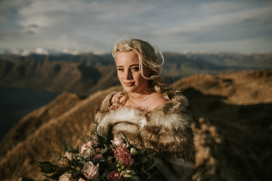 A stunning portrait of a bride on her Wanaka Wedding day. Her blue eyes shine in the sun as she looks out to the distance. She stands on Coromandel Peak, a mountaintop overlooking a lake, with snowcapped mountains in the distance. With photography by Alpine Image Company