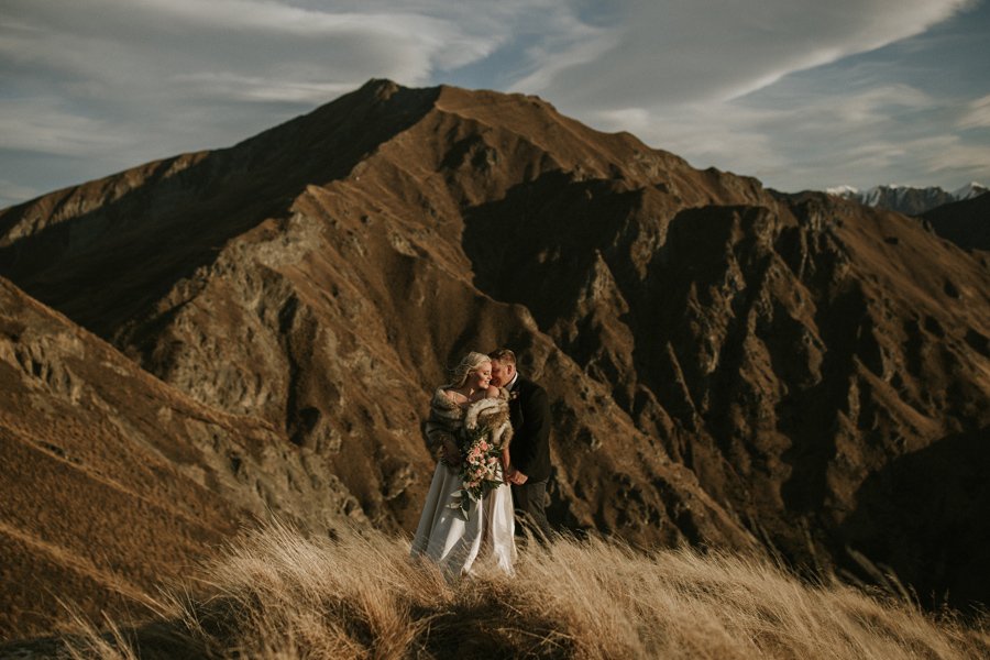 A bride and groom hold each other as the last rays of sunlight hit them. They are standing infront of a jagged mountain, with long grass around their feet. With photography by Alpine Image Company