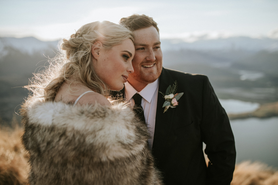 A bride and groom rest their heads against one another as the sun dips behind the mountains on their wedding day. The sky is blue and there are snowcapped mountains in the distance. With photography by Alpine Image Company