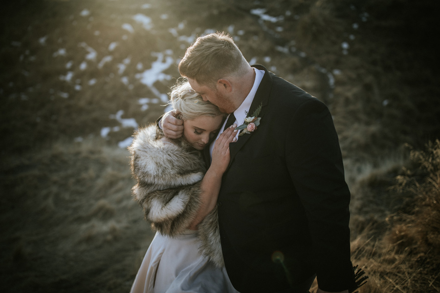 A groom holds his bride close to his heart on their wedding day. The last of the suns rays hit them as they walk back to their helicopter, on their wanaka wedding day. With photography by Alpine Image Company
