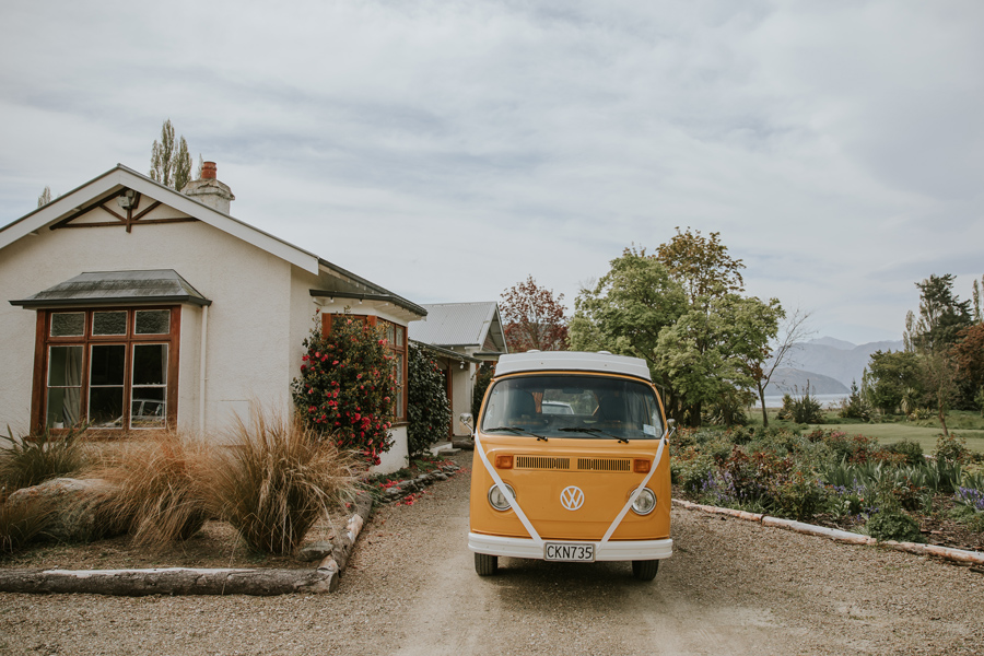 A yellow combi van parks up outside a cottage in New Zealand.