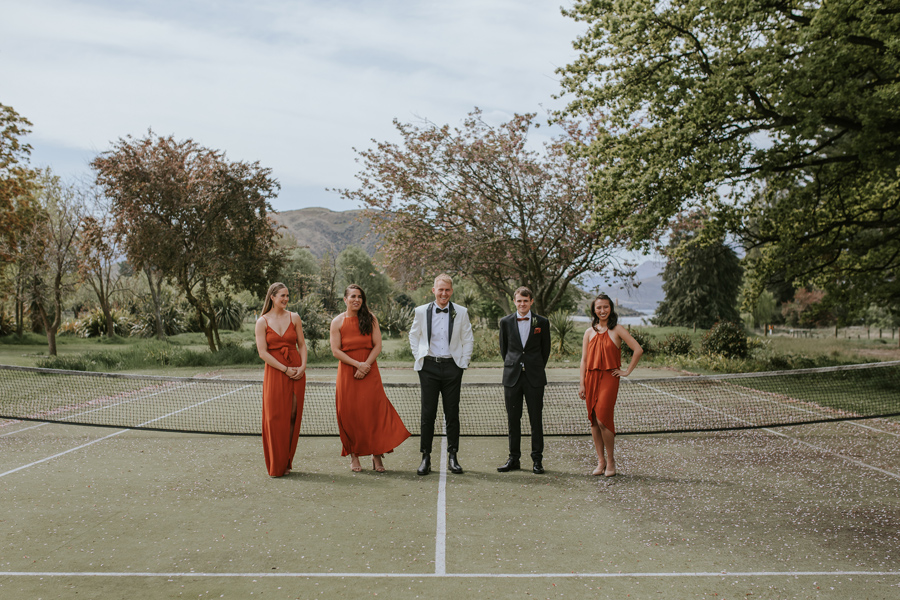 A groom and his bridesmaids stand on a tennis court dressed up in their finery