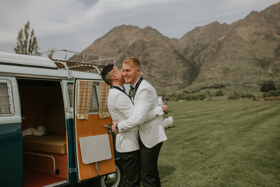 Two grooms embrace in front of a blue combi van. They are smiling and happy and there are mountains in the distance.
