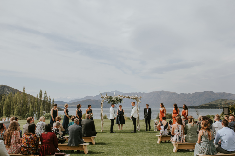 Two grooms stand side by side at their wedding ceremony at Glendu Bay in Wanaka. It is a calm day and the lake and mountains look serene behind them.