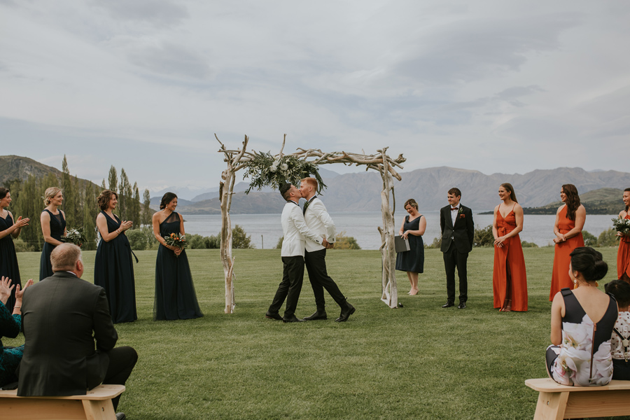 Two grooms share a kiss in front of an archway on their Wanaka Wedding Day. The lake and mountains sit serenly behind them, and the sky is blue with high cloud, making the light soft and beauitufl.