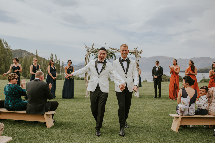 Two grooms hold hands and smile down the aisle on their way out of their wedding ceremony. With photography by Alpine Image Company