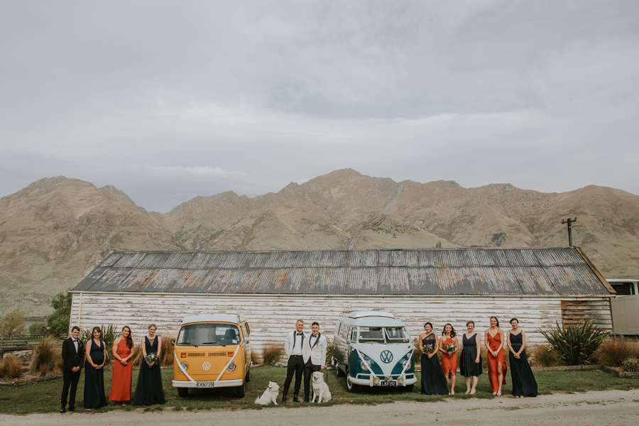 Two grooms and their bridal party stand in front of an old barn at their Wanaka Wedding. They stand between a yellow and a blue combi van, and there are mountains in the background. With photography by Alpine Image Company