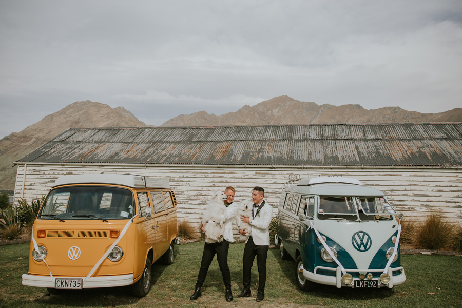 Two grooms stand between a yellow and a blue combi van. There is an old barn and a mountain in the distance, and they are holding their two white dogs. With photography by Alpine Image Company