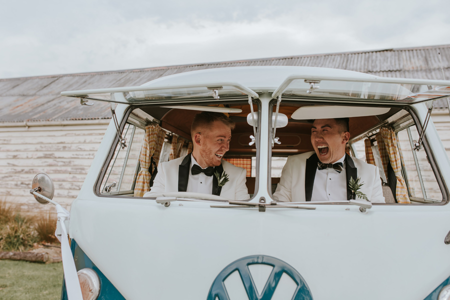Two grooms smile and laugh as they peek through the open windows of their blue combi van on their wedding day. Wtih photography by Alpine Image Company