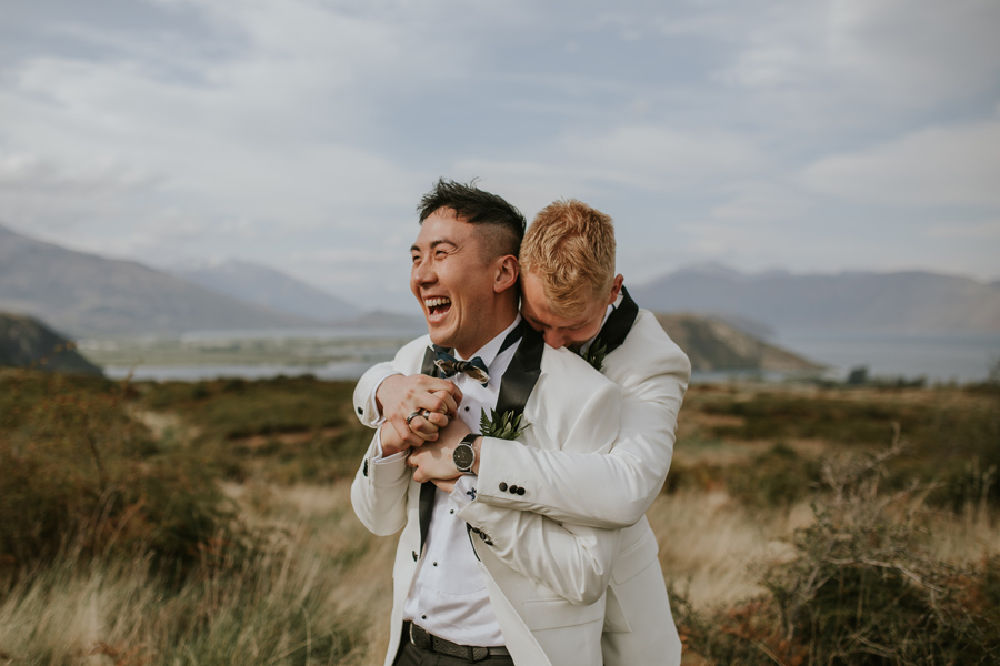 Two grooms embrace and laugh on their Wanaka Wedding Day. The day is calm and the sky blue. They are in a field overlooking lakes and mountains in the distance. With photography by Alpine Image Company