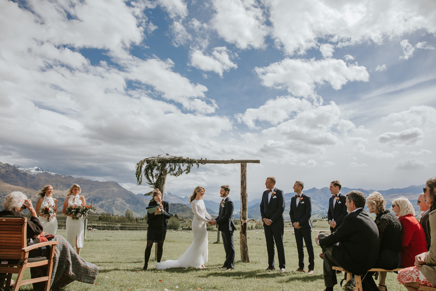 A bride and groom hold hands in front of a wooden arch on their Queenstown Wedding Day. There are mountains and blue sky in the background, and their bridal party stand either side of them. With photography by Alpine Image Company