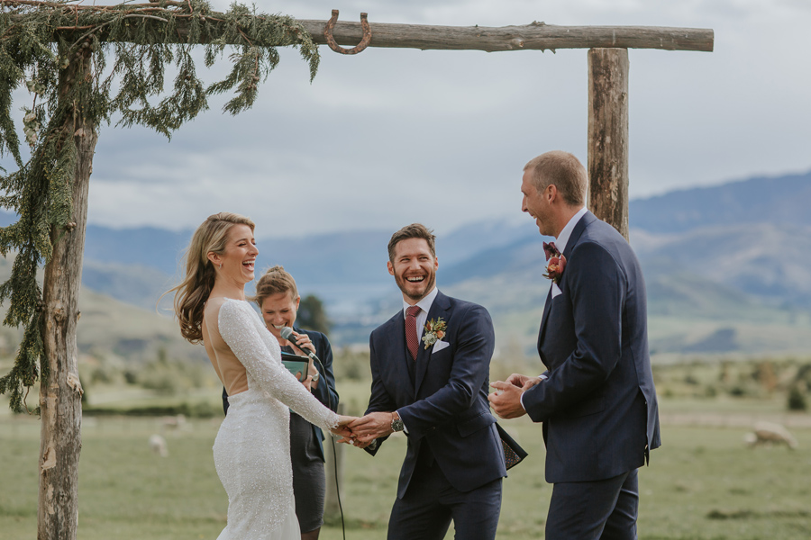 A bride and groom laugh as the best man hands the groom the rings. There are mountains in the background. With photography by Alpine Image Company