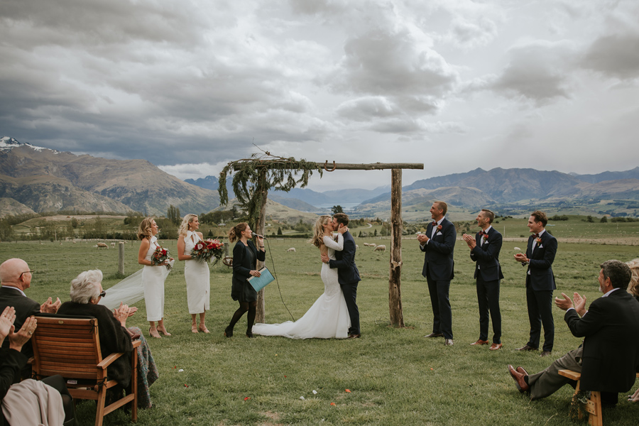 A bride and groom share a first kiss on their Queenstown wedding day. There are mountains in the background and moody cloudy skies. With photography by Alpine Image Company