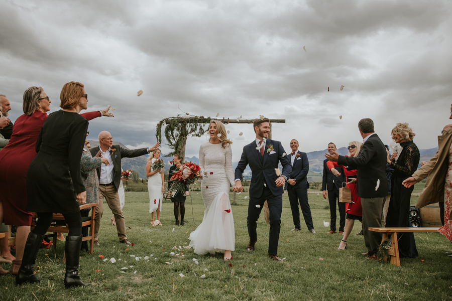A bride and groom laugh as they walk down the aisle on their Queenstown wedding day. There are guests throwing petals over them and the bridal party are laughing. With photography by Alpine Image Company