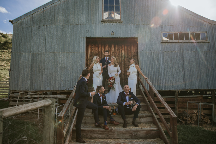 A bridal party laugh with each other as they stand outside a woolshed with the sun setting behind them on a couple's Queenstown wedding day. With photography by Alpine Image Company