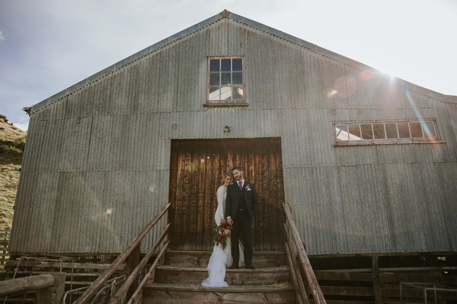 A bride and groom stand poised for their location photos on their wedding day. They are infront of a rustic tin barn, and the sun is setting behind them in the blue sky. With photography by Alpine Image Company
