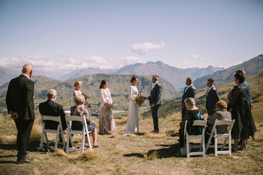 A couple stand holding hands at their Queenstown wedding ceremony. They are on a mountain, with a handful of guests. The sky is blue, and there is a lake a mountain in the background. With photography by Alpine Image Company.