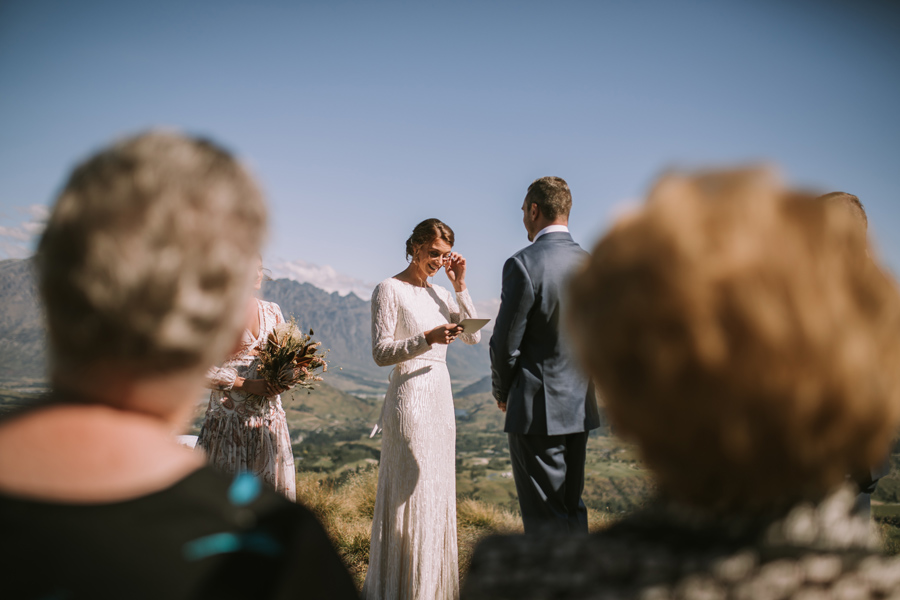 A bride wipes away a tear during her ceremony on her Queenstown Wedding Day. With photography by Alpine Image Company.