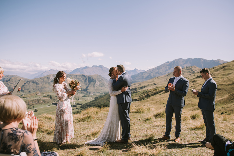 A couple share a first kiss on their Queenstown wedding ceremony. They stand on a mountain, with blue sky and mountains in the distance. With photography by Alpine Image Company.With photography by Alpine Image Company.