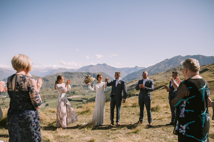 A couple cheer and smile at each other at the end of their Queenstown wedding ceremony. They stand on a mountain, with guests surrounding them. There are mountains and a lake in the distance. The sky is a beautiful blue colour. With photography by Alpine Image Company.