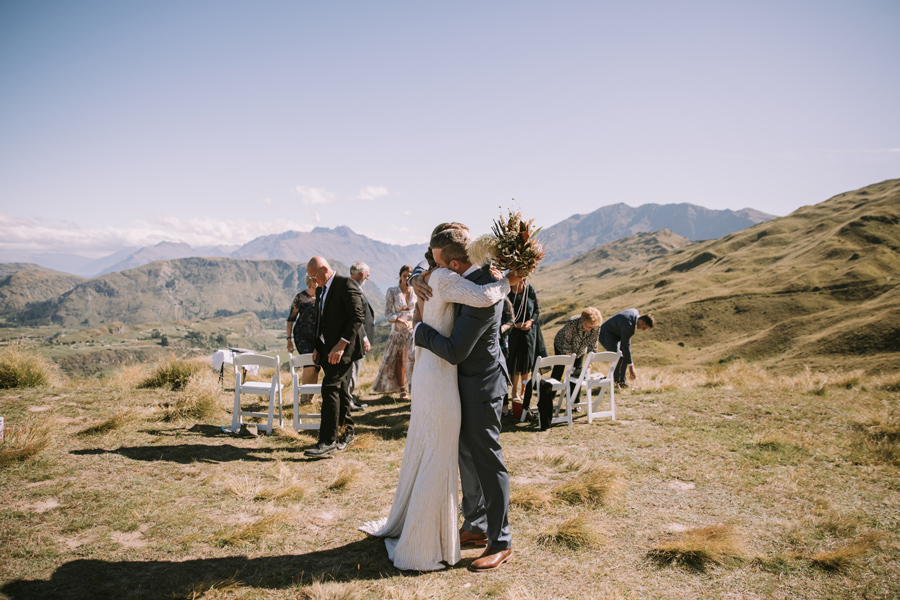 A couple embrace after walking down the ailsle on their wedding day. There are mountains in the background. With photography by Alpine Image Company.
