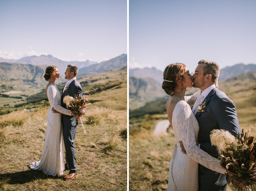 A couple share a kiss on their Queenstown wedding day. The sky is blue, and there are standing on Coronet Peak, and there are mountains in the background. With photography by Alpine Image Company.