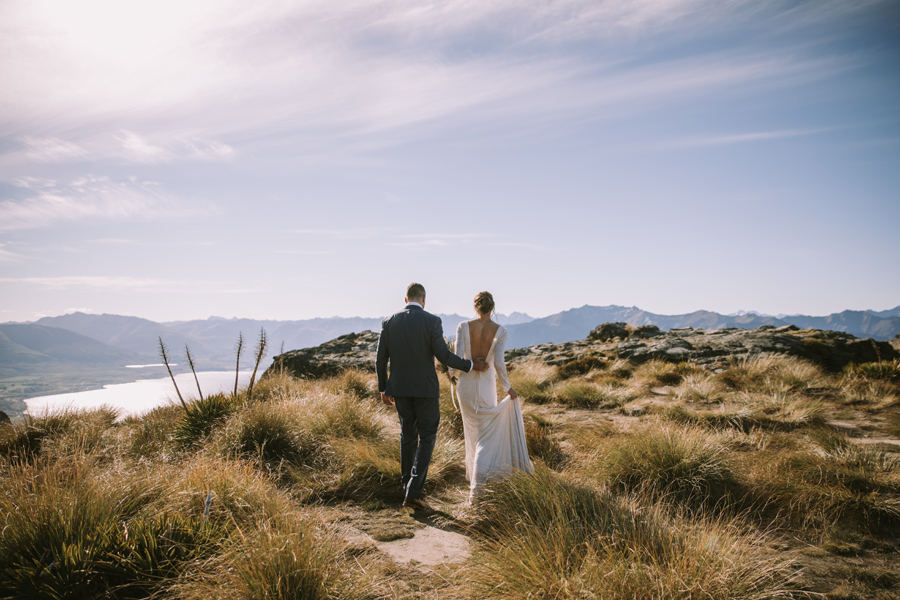 A couple walk into the distance on their wedding day. The groom has his arm around the brides waist. There are mountains and a lake in the background. With photography by Alpine Image Company.