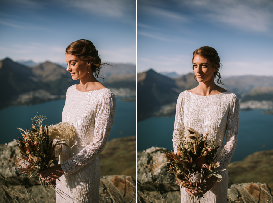 A bride look down towards her flowers on her Queenstown wedding day. She is standing on Cecil Peak, and there is a lake and mountains in the distance. With photography by Alpine Image Company.