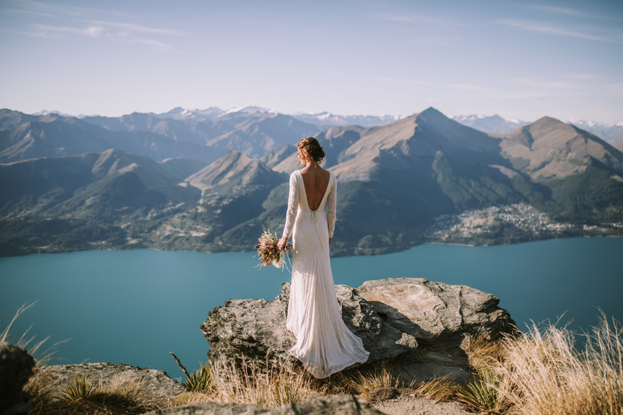 A bride looks out at the veiw on top of a mountain, on her Queenstown wedding day. The lake below her is a beautiful turquoise blue, and there are mountains in the distance. With photography by Alpine Image Company.