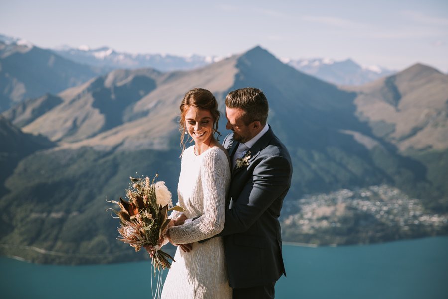 A bride and groom embrace on their Queenstown wedding day. They are standing on Cecil Peak, with mountains and a lake in the distance. With photography by Alpine Image Company.